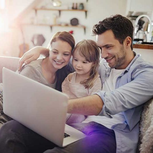 Family sitting together with a laptop